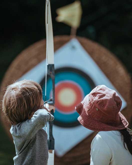 Niños apuntando a una diana. Metáfora de cómo se concretan los objetivos en Coaching personal.