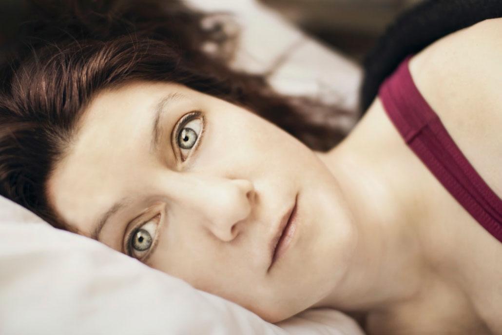 Mujer en la cama con los ojos abiertos porque no puede dormir.