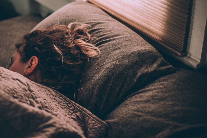 Mujer en la cama durmiendo.