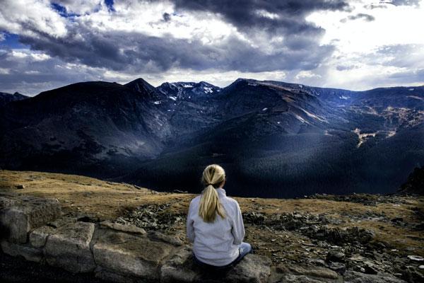 Mujer sentada frente a unas montañas nevadas en posición de meditación Mindfulness.