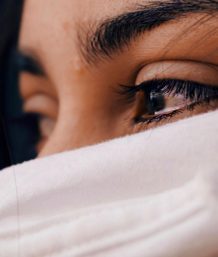 Primer plano de una mujer con mascarilla. Ojos llorosos expresando tristeza.