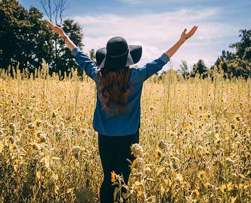 Mujer respaldas en un campo de girasoles con los brazos abiertos. Agradeciendo la maravilla de la naturaleza.