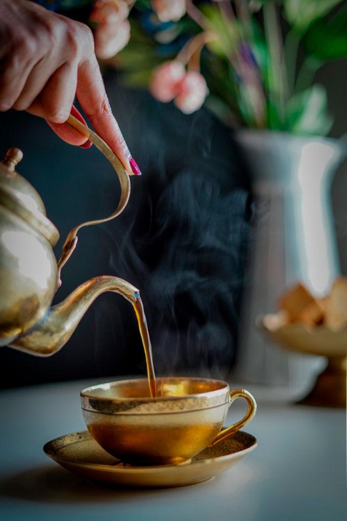 Mano vertiendo té en una taza. Sentimiento de agradecimiento ante un té caliente.