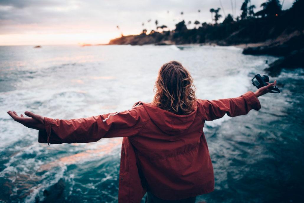 Mujer frente al mar con los brazos abiertos. Soltando el control para sentirse más libre.