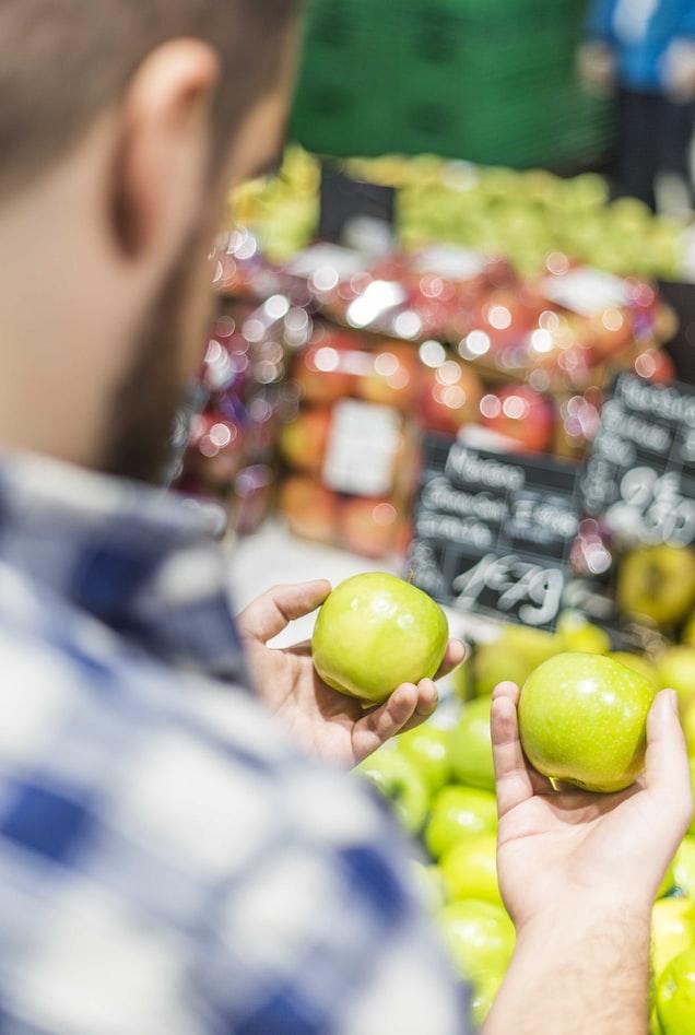 Hombre en el supermercado con una manzana verde en cada mano. Como tomar decisiones.