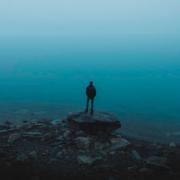 Chico subido a una piedra mirando hacia un lago de un azul intenso. Blue day.