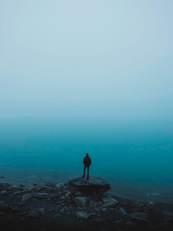Hombre subido en una rato mirando hacia un lago azul. Sensación de tristeza y depresión. Blue day.