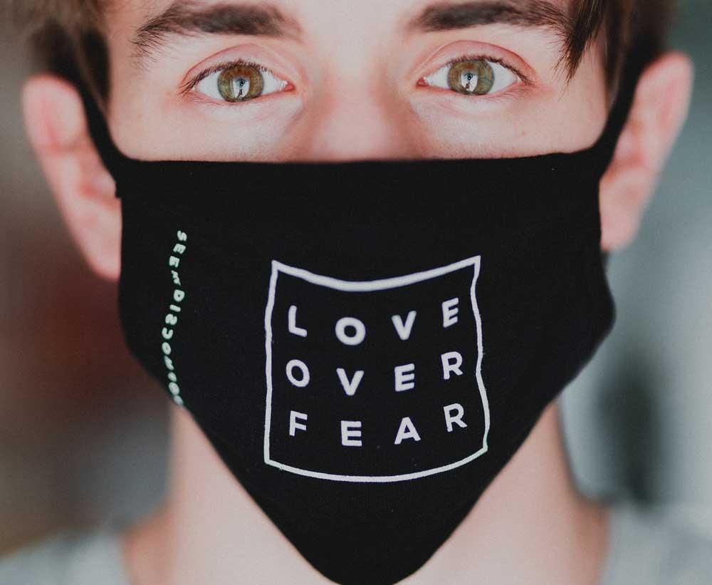 Hombre con mascarilla: Love over Fear. Amor frente a miedo.
