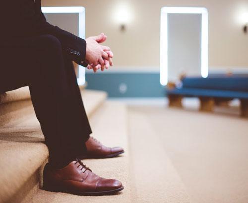Hombre en traje en una sala de espera con las manos cruzadas.