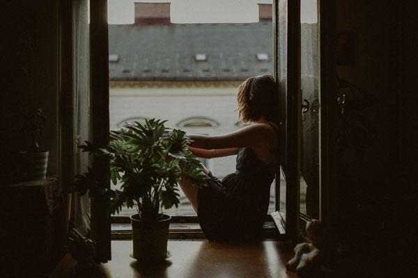 Mujer mirando por la ventana con tristeza